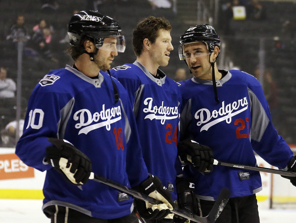 Photo - From left, Los Angeles Kings center Mike Richards (10), center Colin Fraser (24) and defenseman Alec Martinez (27) talk during warmups while wearing Los Angeles Dodgers jerseys before an NHL hockey game against the Columbus Blue Jackets in Los Angeles, Thursday, April 18, 2013. (AP Photo/Reed Saxon)