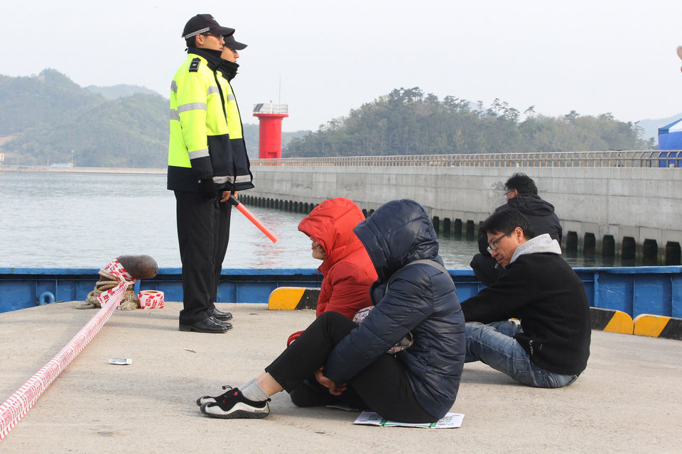 Photo - Relatives of passengers aboard the sunken Sewol ferry wait for their missing loved ones at a port in Jindo, South Korea, Tuesday, April 22, 2014.  As divers continue to search the interior of the sunken ferry, the number of confirmed deaths has risen, with about 220 other people still missing.  (AP Photo/Ahn Young-joon)