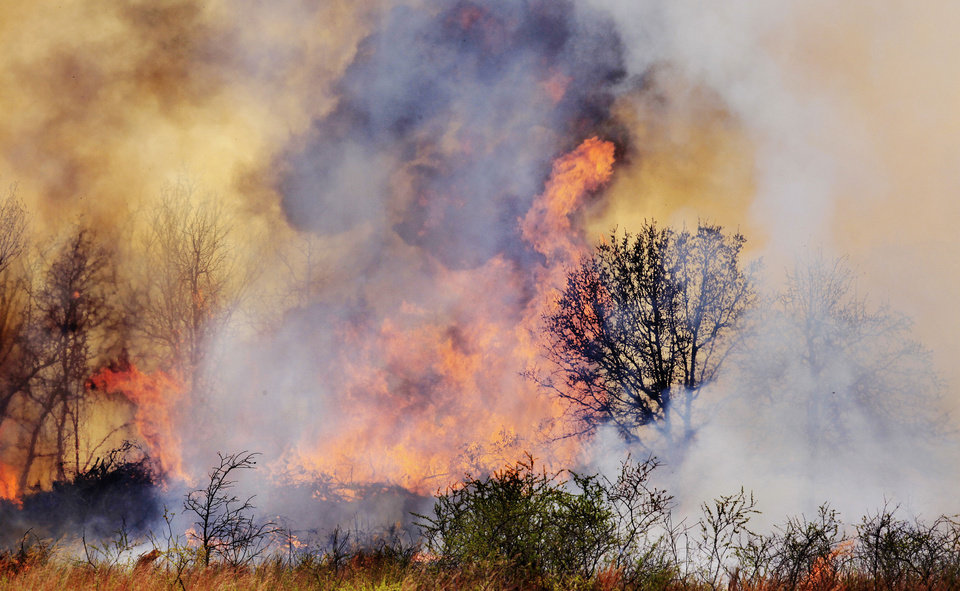 Photo - A grass fire moves through a field in 2011 at NE 73 and Post Road in Oklahoma City.  Photo by PAUL B. SOUTHERLAND, THE OKLAHOMAN ARCHIVES