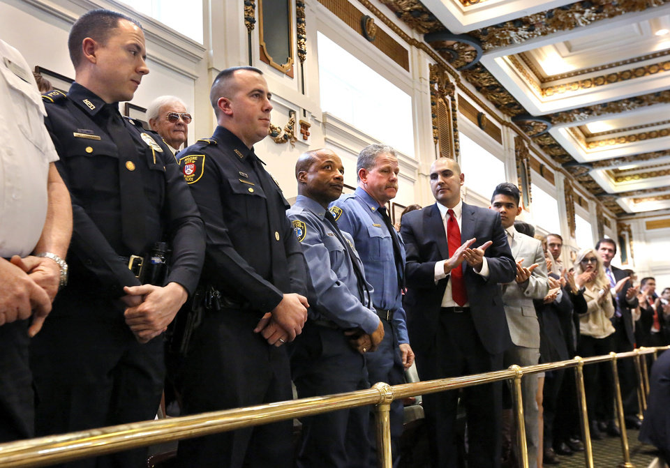 Photo - Representatives from Moore police and fire departments stand as the governor and lawmakers acknowledge the heroic actions performed by first responders during the  outbreak of deadly tornadoes  in central Oklahoma in May, 2013. Gov. Mary Fallin outlined her goals for the upcoming legislative session during her state of the state speech to a joint session of the legislature in the House chamber at the state Capitol on Monday, Feb. 3, 2014.   Photo by Jim Beckel, The Oklahoman