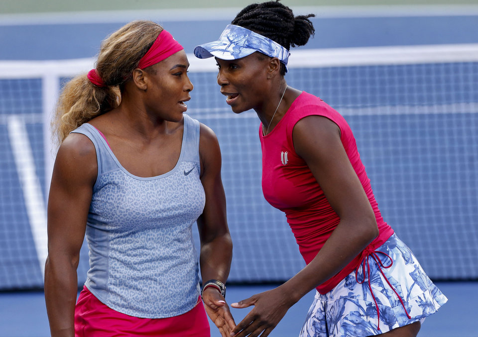 Photo - Serena Williams, left, and Venus Williams talk between points against Timea Babos and Kristina Mladenovic during a doubles match at the 2014 U.S. Open tennis tournament, Thursday, Aug. 28, 2014, in New York. (AP Photo/Matt Rourke)