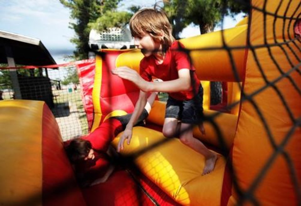Photo -  Luke Ozment, 10 of Norman, races his brother on the bouncy castle obstacle course at Reaves Park in Norman on July 4, 2013 for Norman's annual Independence Day celebration. Photo by K.T. KING, The Oklahoman