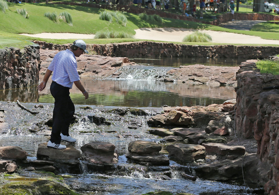 Photo - Gene Sauers walks across a creek to the fifth tee during the final round of the U.S. Senior Open golf tournament at Oak Tree National in Edmond, Okla., Sunday, July 13, 2014. (AP Photo/Sue Ogrocki)