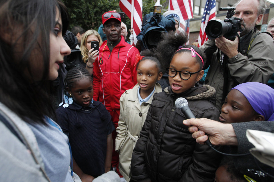 Samantha Pawlucy, left, listens to a group of cousins recite the Declaration of Independence during a rally in support of her as she returned to school on Tuesday, Oct. 9, 2012 in Philadelphia. The young girls from left are Amerie Harris, 9, La'Joir Coppock, 8, Laija Coppock, 10, and Amani Harris, 9. They were accompanied by their grandfather, in red, background center, Lewis Harris. Pawlucy had stayed home after she was allegedly singled out by a teacher for wearing a Mitt Romney t-shirt to school. THE EVENING BULLETIN OUT, TV OUT; MAGS OUT; NO SALES