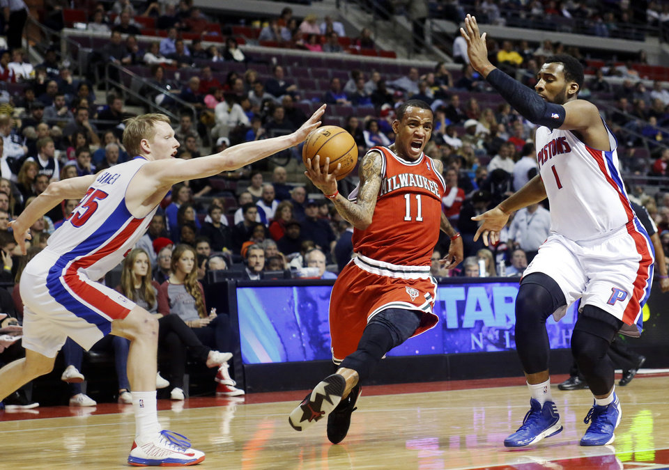 Photo - Milwaukee Bucks guard Monta Ellis (11) splits the defense of Detroit Pistons forwards Kyle Singler, left, and Andre Drummond (1) while driving to the basket in the first half of an NBA basketball game, Sunday, Dec. 30, 2012, in Auburn Hills, Mich. (AP Photo/Duane Burleson)