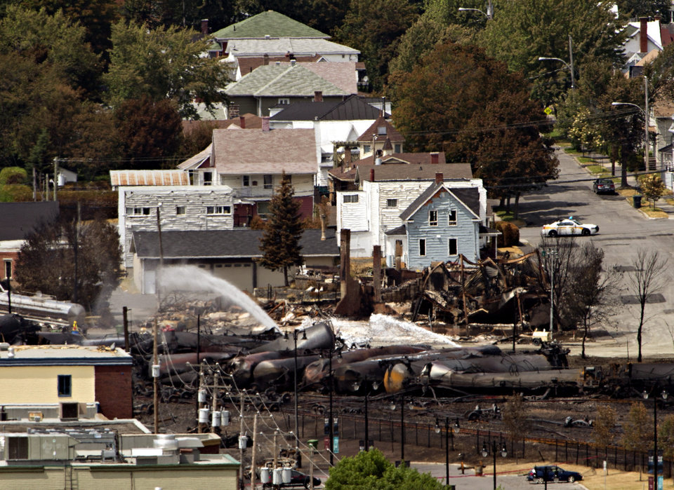 Photo - Wreckage is strewn through the downtown core in Lac-Megantic, Quebec, Monday, July 8, 2013, after a train derailed, igniting tanker cars carrying crude oil early Saturday. (AP Photo/The Canadian Press, Ryan Remiorz)