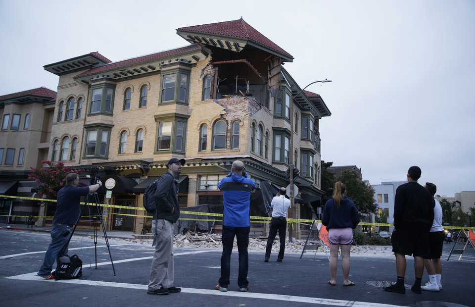 Photo - People look at a damaged building with a top corner exposed following an earthquake Sunday, Aug. 24, 2014, in Napa, Calif. A large earthquake rolled through California's northern Bay Area early Sunday, damaging some buildings, igniting fires, knocking out power to tens of thousands and sending residents running out of their homes in the darkness. (AP Photo/Eric Risberg)