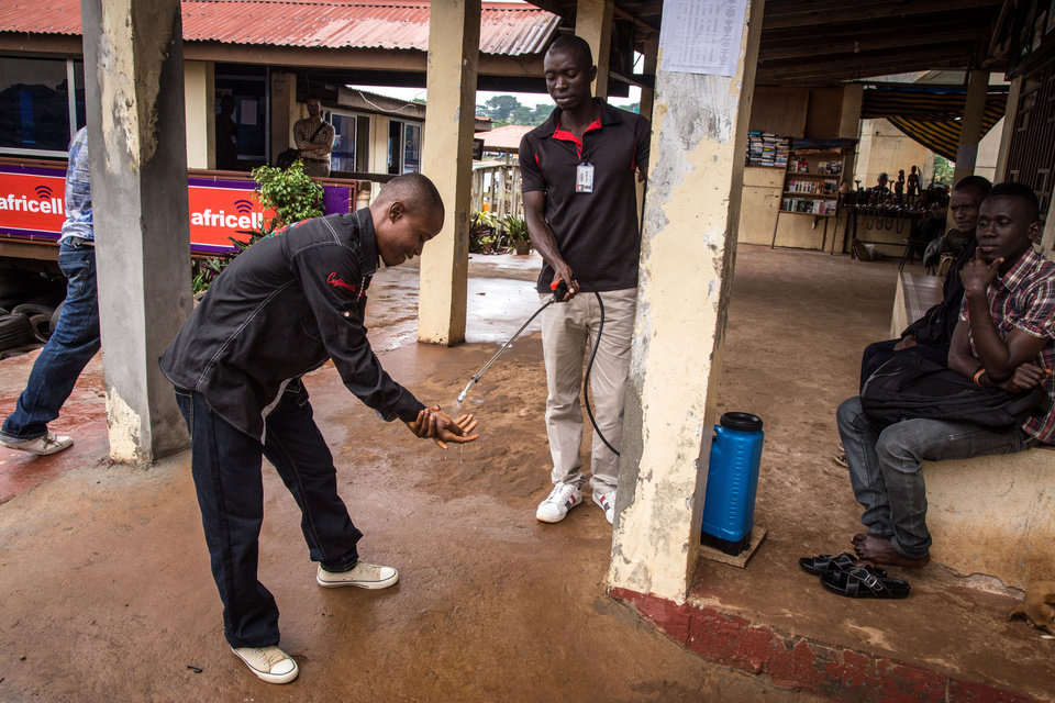 Photo - A health worker, center, washes the hands of a man, left, before he enters a building as part of an Ebola prevention campaign in the city of Freetown, Sierra Leone, Wednesday, Aug. 6, 2014.  The World Health Organization has begun an emergency meeting on the Ebola crisis, and said at least 932 deaths in four African countries are blamed on the virus, with many hundreds more being treated in quarantine conditions. (AP Photo/ Michael Duff)