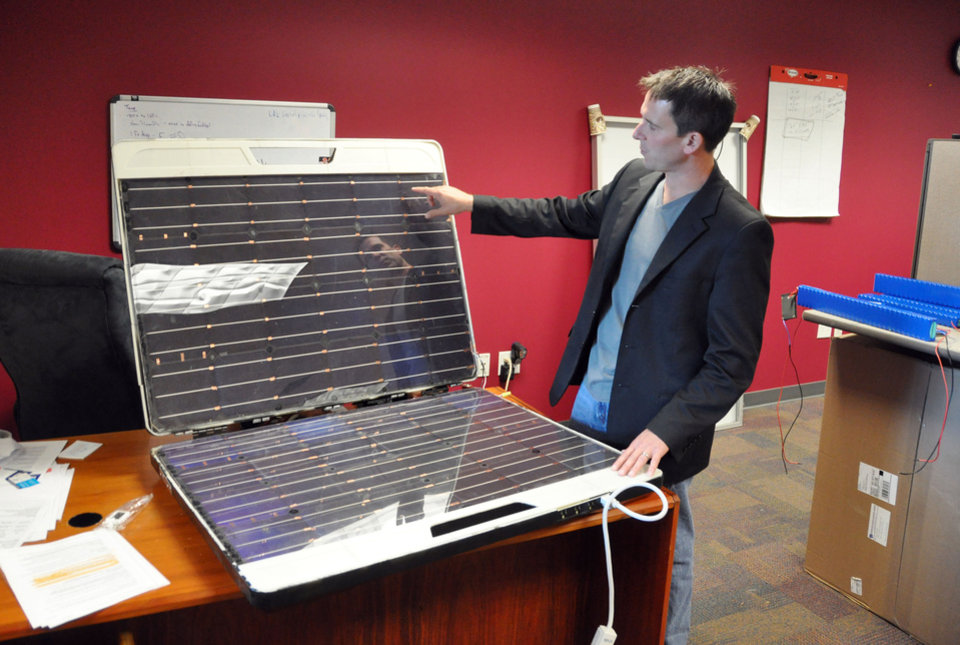 "In this Friday, Sept. 14, 2012 photo, Brian Gramm, chief executive of Peppermint Clean Energy, shows off a protype of the Forty2, in Sioux Falls, S.D. Gramm said the all-in-one ""utility in a box"" can generate and store enough solar power to run a dorm fridge filled with medicine around the clock in a remote African village. (AP Photo/Dirk Lammers)"
