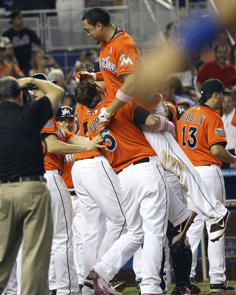 Photo -   Miami Marlins' Logan Morrison (5) hoists teammate Giancario Stanton into the air after Stanton hit the game-winning grand slam against the New York Mets in the ninth inning of a baseball game in Miami, Sunday, May 13, 2012. The Marlins defeated the Mets 8-4. (AP Photo/J Pat Carter)