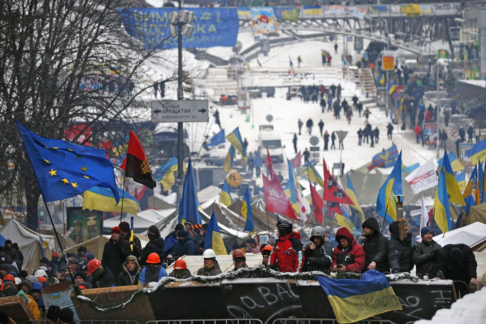 Photo - Pro-European Union activists get ready to defend their tent camp on the Independence Square in Kiev, Ukraine, Monday, Dec. 9, 2013. The policemen, wearing helmets and holding shields, formed a chain across Kiev's main street outside the city building. Organizers called on protesters to vacate the city hall and the other building which the opposition had used as its headquarters. (AP Photo/Alexander Zemlianichenko)