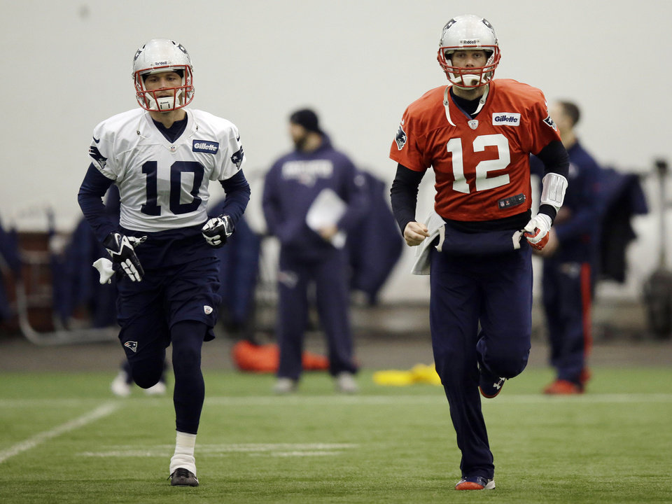 Photo - New England Patriots quarterback Tom Brady (12) and wide receiver Austin Collie (10) run during a stretching session before NFL football practice at the team's facility in Foxborough, Mass., Tuesday, Jan. 7, 2014. The Patriots are scheduled to host the Indianapolis Colts in an NFL football divisional playoff game on Saturday, Jan. 11. (AP Photo/Stephan Savoia)