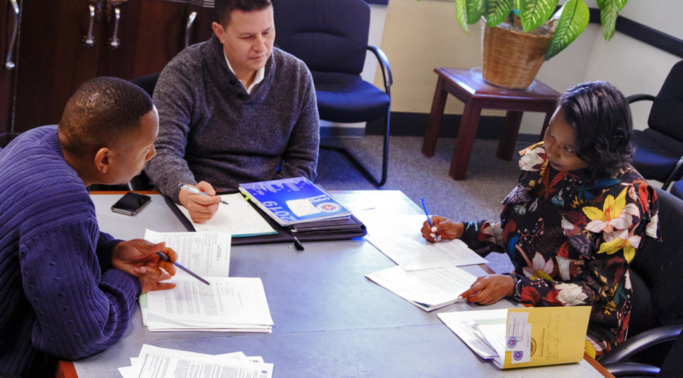 Photo - New Oklahoma City Ward 7 councilwoman Nikki Nice goes over paper work with Christian York, center, and Ziven Vaughn as she begins her new position on the city council at the City of Oklahoma City's City Council office in Oklahoma City, Okla. on Friday, Nov. 9, 2018. Photo by Chris Landsberger, The Oklahoman