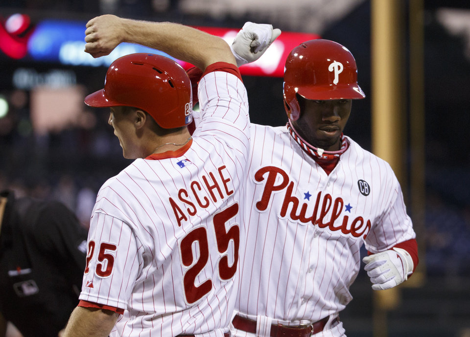 Photo - Philadelphia Phillies' Domonic Brown, right, celebrates his two-run homer with Cody Asche during the fourth inning of a baseball game against the Cincinnati Reds, Saturday, May 17, 2014, in Philadelphia. (AP Photo/Chris Szagola)