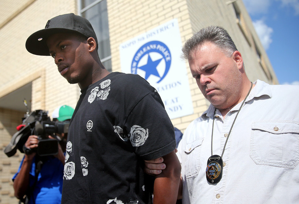 Photo - Shawn Scott, left, who with his younger brother Akien is accused of the Mother's Day second-line shooting which injured 20 people, is taken from the 5th District Police Station to Orleans Parish Prison in New Orleans on Thursday, May 16, 2013.    (AP Photo/The Times-Picayune, Michael DeMocker ) MAGS OUT; NO SALES; USA TODAY OUT; THE BATON ROUGE ADVOCATE OUT