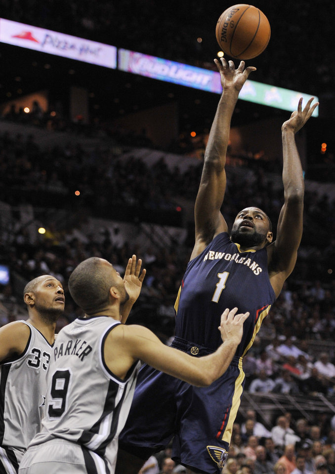 Photo - New Orleans Pelicans forward Tyreke Evans, right, shoots against San Antonio Spurs guard Tony Parker (9) and forward Boris Diaw, both of France, during the first half of an NBA basketball game on Saturday, March 29, 2014, in San Antonio. (AP Photo/Darren Abate)