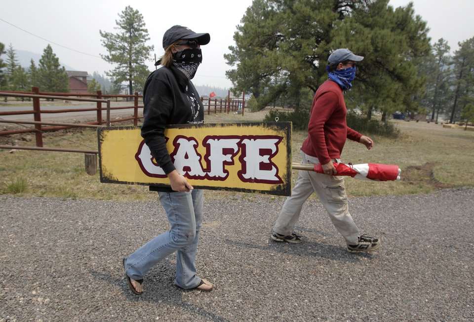 Photo -   Kristi Spillman, left, and her boyfriend Michael Carter Jr. wear bandanas as they gather their belongings in Greer, Ariz., Sunday, June 5, 2011. Crews used controlled backfires early Sunday to blunt the advance of a major wildfire near mountain communities in eastern Arizona, a blaze termed