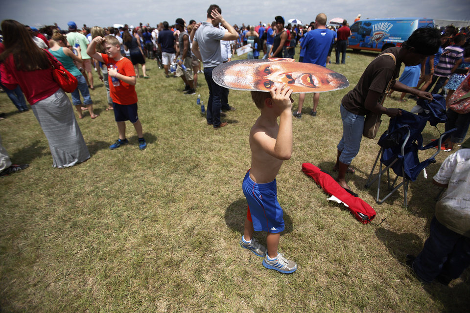 Photo - Jack Pitman, 11, of Oklahoma City, shades himself from the sun during a welcome home rally for the Oklahoma City Thunder at a field near Will Rogers Airport in Oklahoma City, Friday, June 22, 2012.  Photo by Garett Fisbeck, The Oklahoman