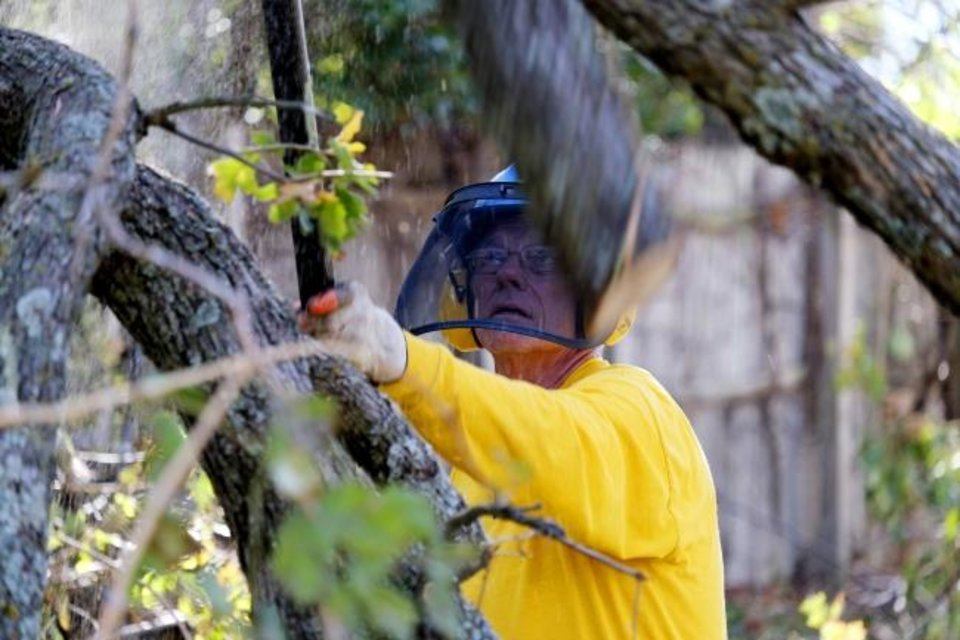 Photo -  An Oklahoma Baptists Disaster Relief crew member works on tree limb removal on Friday at a Bethany home. [Doug Hoke/The Oklahoman]