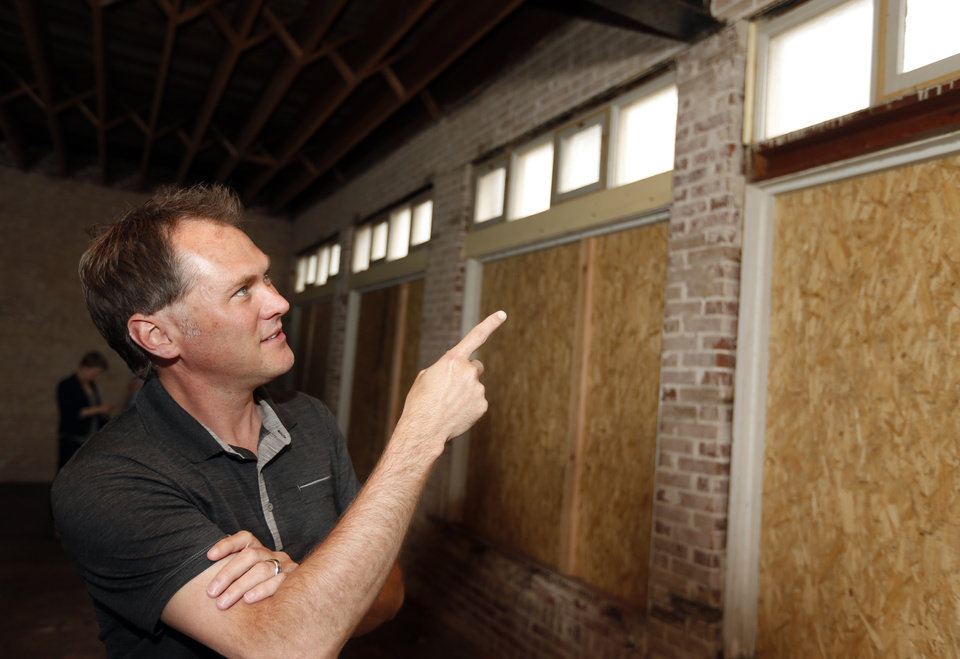Photo -  Developer David Wanzer shows transom windows dating to construction of the former Blair's Upholstery building  that were covered up for decades before recently being opened up as part of a renovation of the property for a new craft beer restaurant and ice cream shop. Photo by Nate Billings, The Oklahoman   NATE BILLINGS -