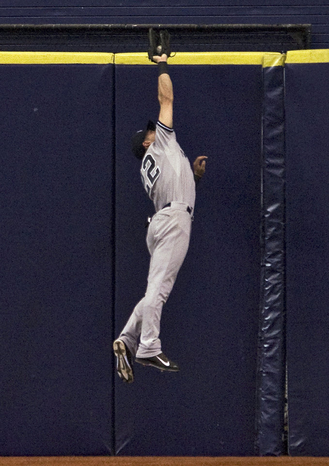 Photo - New York Yankees center fielder Jacoby Ellsbury robs Tampa Bay Rays' Ben Zobrist of an extra-base hit during the fourth inning of a baseball game Friday, April 18, 2014, in St. Petersburg, Fla. (AP Photo/Steve Nesius)