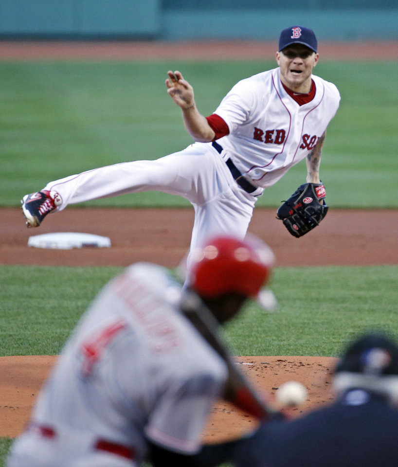 Photo - Boston Red Sox starting pitcher Jake Peavy, back, delivers to Cincinnati Reds' Brandon Phillips during the first inning of a baseball game at Fenway Park in Boston, Wednesday, May 7, 2014. (AP Photo/Elise Amendola)