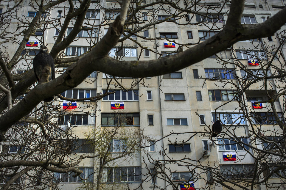 Photo - Russian flags are hung out on an apartment building in a residential district in Sevastopol, Ukraine, Friday, March 14, 2014. Crimea plans to hold a referendum on upcoming Sunday that will ask residents if they want the territory to become part of Russia. Ukraine's government and Western nations have denounced the referendum as illegitimate and warned Russia against trying to annex Crimea. (AP Photo/Andrew Lubimov)