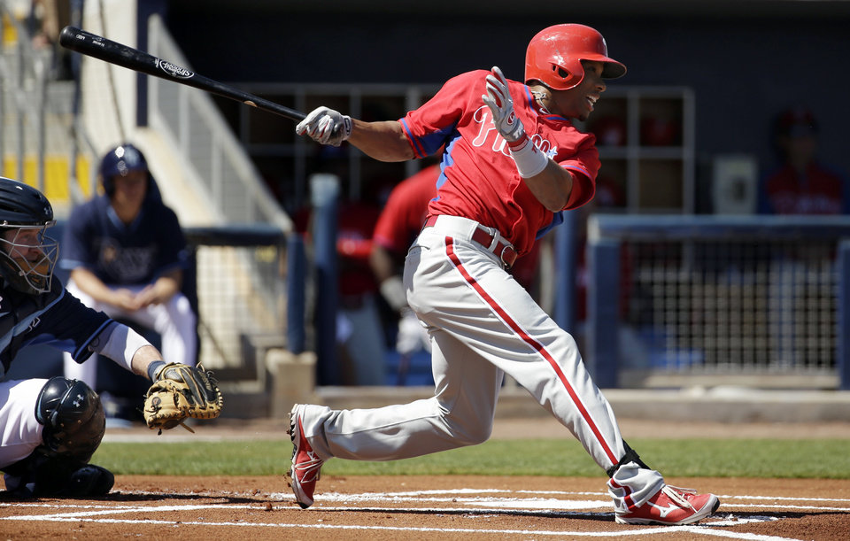 Photo - Philadelphia Phillies' Ben Revere, right, singles off a pitch by Tampa Bay Rays' Matt Moore in front of Rays catcher Ryan Hanigan, left, in the first inning an exhibition baseball game, Monday, March 3, 2014, in Port Charlotte, Fla. (AP Photo/Steven Senne)