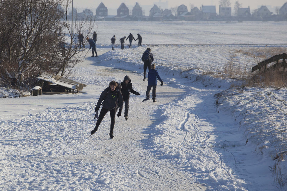 Photo - FILE - In this Feb. 4, 2012, file photo, skaters enjoy the sun and frozen canals in the village of Ransdorp, north of Amsterdam. There is nothing more mythical in Dutch sports than an age-old 11-city race skating across lakes and canals in bone-numbing cold from dawn to dusk. No wonder the Netherlands is the greatest speedskating nation in the world. And with Sven Kramer and Ireen Wust leading the way on big oval in Sochi they are bent on proving it again.  (AP Photo/Peter Dejong, File)