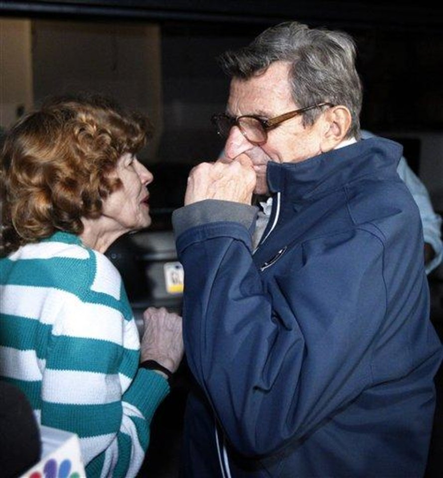 Photo - Penn State football coach Joe Paterno and his wife, Sue Paterno, react after he arrived at his home, Tuesday, Nov. 8, 2011, in State College, Pa. Paterno's support among the Penn State board of trustees was described as