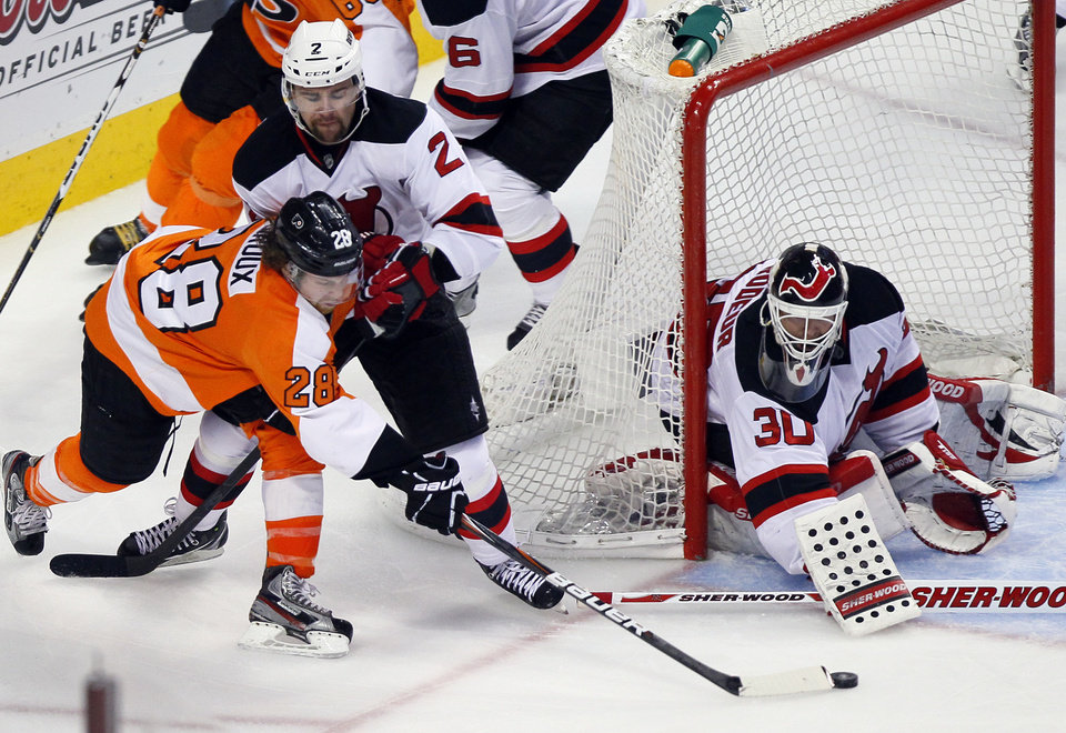 Photo -   New Jersey Devils' Marek Zidlicky, rear, pushes on Philadelphia Flyers' Claude Giroux (8) trying to make a wrap-around shot as goalie Martin Brodeur defend the crease during the third period in Game 2 of an NHL hockey Stanley Cup second-round playoff series, Tuesday, May 1, 2012, in Philadelphia. The Devils won 4-1 evening the best of seven series at 1-1.(AP Photo/Tom Mihalek)