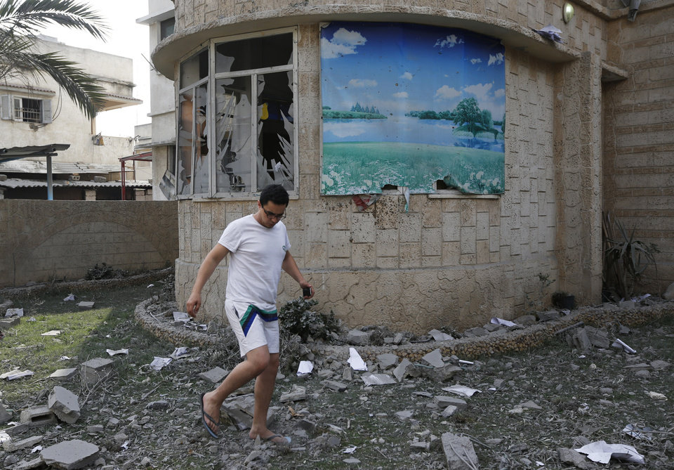 Photo - A man walks on debris from his damaged house, hit by an overnight Israeli strike, in Gaza City, Monday, July 21, 2014. On Sunday, the first major ground battle in nearly two weeks of Israel-Hamas fighting exacted a steep price, killing scores Palestinians and over a dozen Israeli soldiers and forcing thousands of terrified Palestinian civilians to flee their devastated Shijaiyah neighborhood, which Israel says is a major source for rocket fire against its civilians. (AP Photo/Lefteris Pitarakis)
