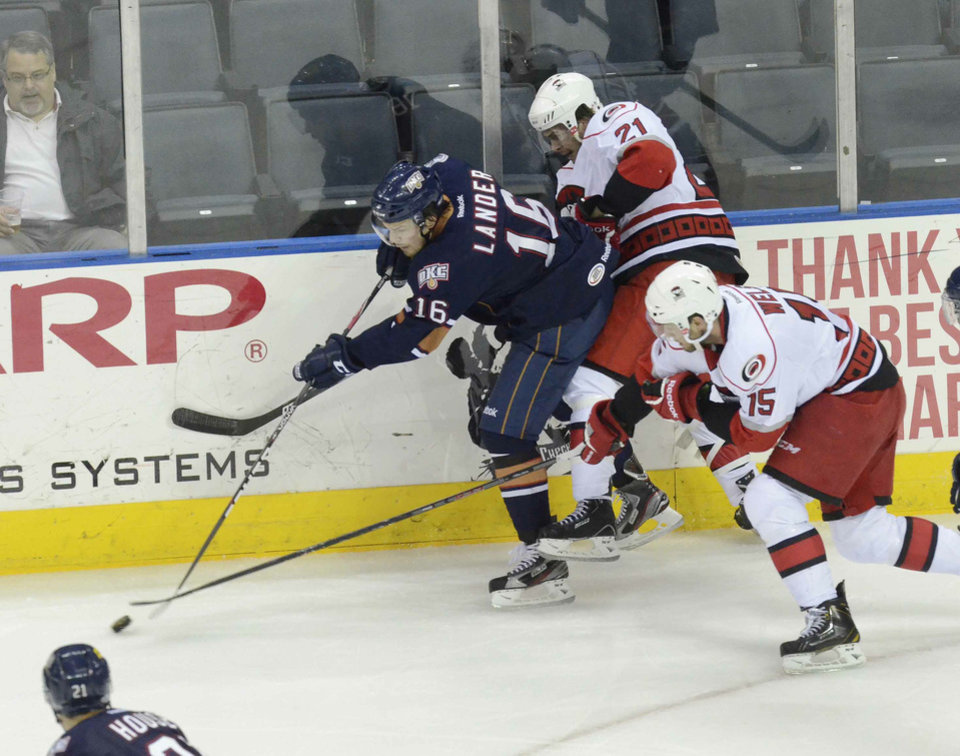 Oklahoma City Barons Anton Lander, left, chases after the puck against Charlotte Checkers Jeremy Welsh, right, during Wednesday night's Game 3 of the best-of-five American Hockey League playoff series played at Time Warner Cable Arena May 01,2013. PHOTO BY ROBERT LAHSER, COURTESY CHARLOTTE OBSERVER <strong>Robert Lahser</strong>