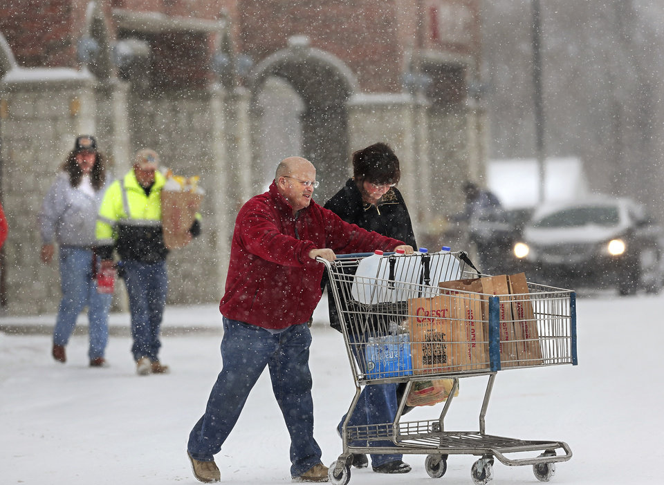 Photo - Shoppers return to their cars in the parking lot of Crest Foods in Midwest City. Snow began falling in central Oklahoma around 7 Sunday morning, Feb. 2, 2014.   Photo by Jim Beckel, The Oklahoman
