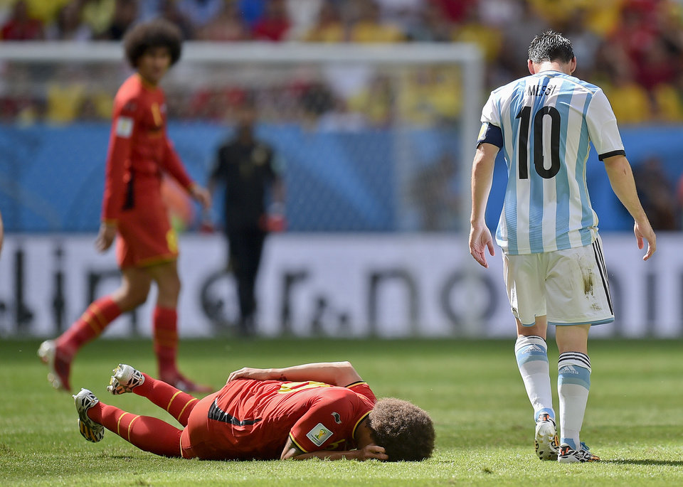 Photo - Argentina's Lionel Messi, right, walks away after fouling Belgium's Axel Witsel during the World Cup quarterfinal soccer match between Argentina and Belgium at the Estadio Nacional in Brasilia, Brazil, Saturday, July 5, 2014. (AP Photo/Martin Meissner)