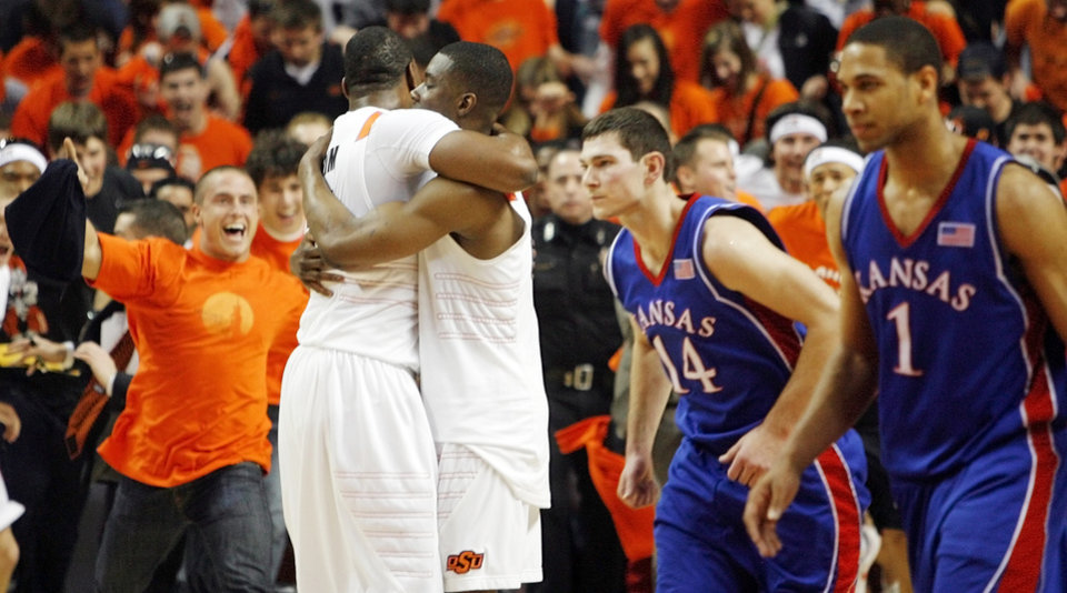Photo - OSU fans take the court as Matt Pilgrim (31), left, and Obi Muonelo (2) hug, while KU's Tyrel Reed (14) and Xavier Henry (1) leave the court at the end of the men's college basketball game between the University of Kansas (KU) and Oklahoma State University (OSU) at Gallagher-Iba Arena in Stillwater, Okla., Saturday, Feb. 27, 2010. OSU won, 85-77. Photo by Nate Billings, The Oklahoman
