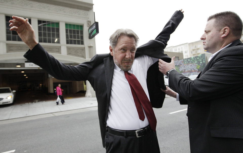 Photo -   Oracle CEO Larry Ellison, left, puts on his suit as arrives for a court appearance at a federal building in San Francisco, Tuesday, April 17, 2012. Oracle intends to rely heavily on Google's own internal emails to prove Google's top executives knew they were stealing a popular piece of technology to build the Android software that now powers more than 300 million smart phones and tablet computers. (AP Photo/Paul Sakuma)