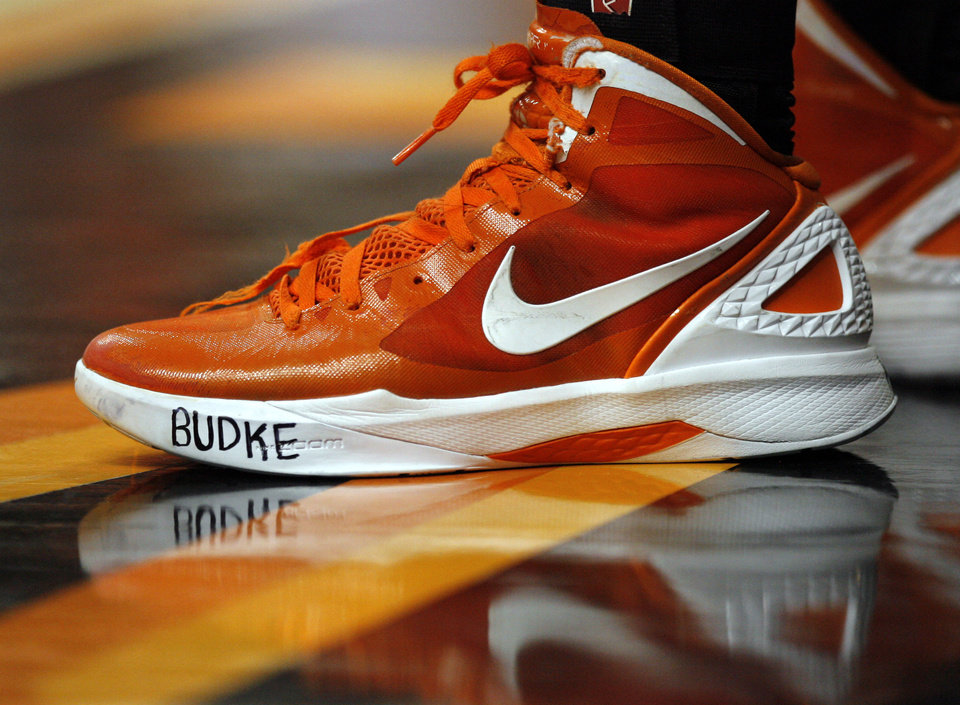 Photo - An Oklahoma State player wears a sneaker with Coach Kurt Budke's name in his memory during the women's college game between Oklahoma State University and Coppin State at Gallagher-Iba Arena in Stillwater, Okla.,  Saturday, Nov. 26, 2011.  Oklahoma State won its first game since a plane crash killed coach Kurt Budke, assistant coach Miranda Serna and two others, topping Coppin State 59-35 on Saturday. Photo by Sarah Phipps, The Oklahoman