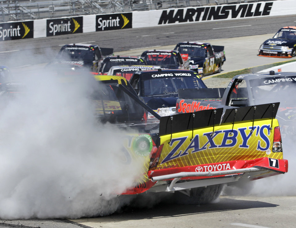 Photo - Driver John West Townley (7) spins into the wall in Turn 4 during the Kroger 250 NASCAR Truck series auto race at Martinsville Speedway in Martinsville, Va., Saturday, April 6, 2013. (AP Photo/Steve Helber)