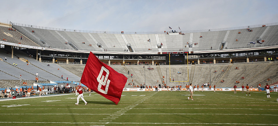 A member of the Oklahoma Ruf/Neks waves the OU flag before the start of the Red River Rivalry college football game between the University of Oklahoma Sooners (OU) and the University of Texas Longhorns (UT) at the Cotton Bowl Stadium in Dallas, Saturday, Oct. 12, 2013. Photo by Chris Landsberger, The Oklahoman