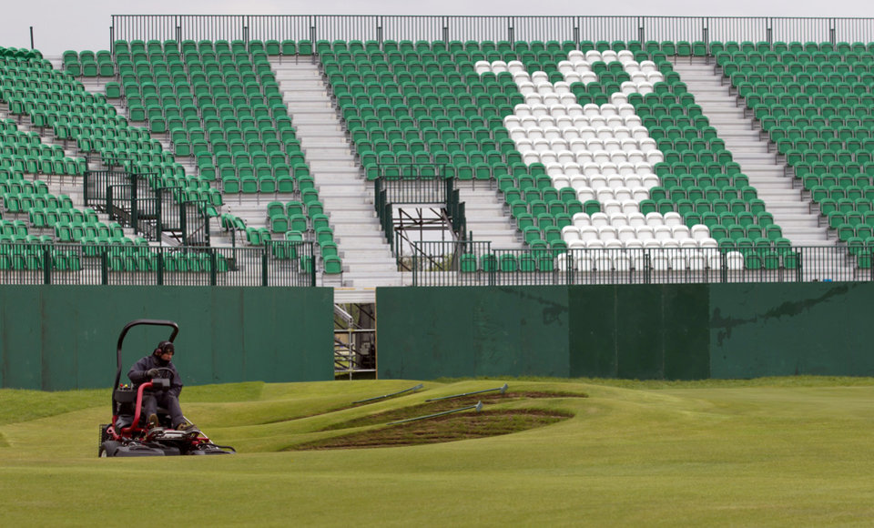 Photo - FILE - In this April 23, 2014, file photo, greenkeeper mows the grass on the 18th green at Royal Liverpool Golf Club in Hoylake, England. The British Open golf championship begins on Thursday July 17, 2014. (AP Photo/Jon Super, File)