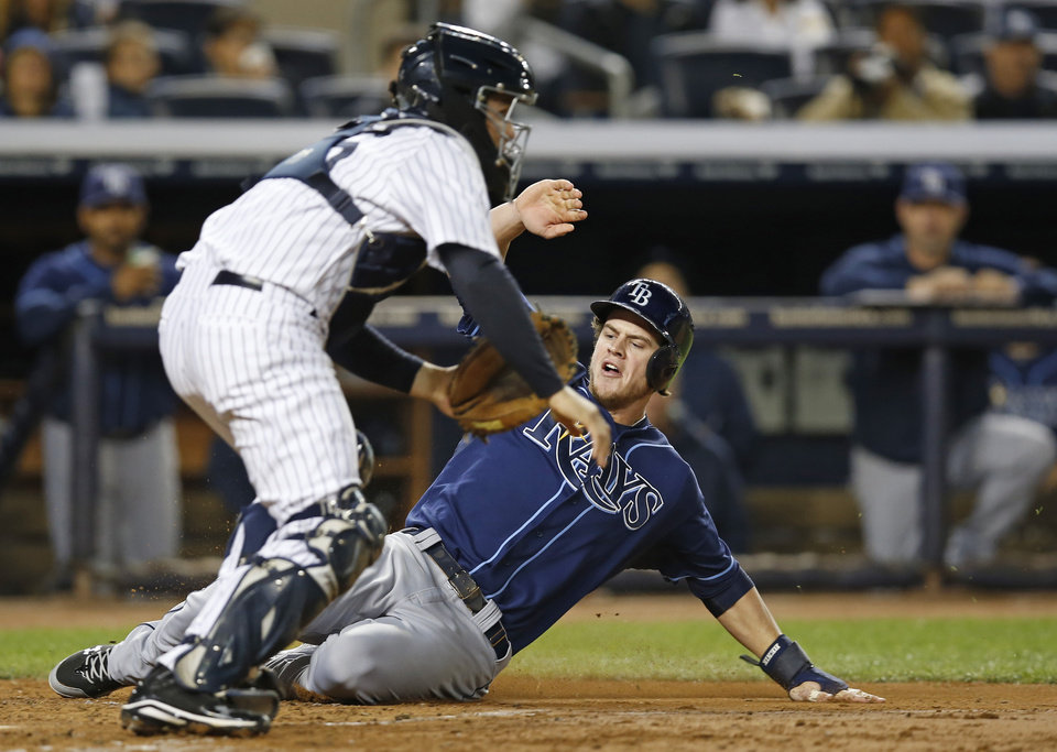 Photo - Tampa Bay Rays' Wil Myers scores on Evan Longoria's fourth-inning RBI single, sliding in ahead of the throw to New York Yankees catcher J.R. Murphy in a baseball game, Thursday, Sept. 26, 2013, in New York. (AP Photo/Kathy Willens)