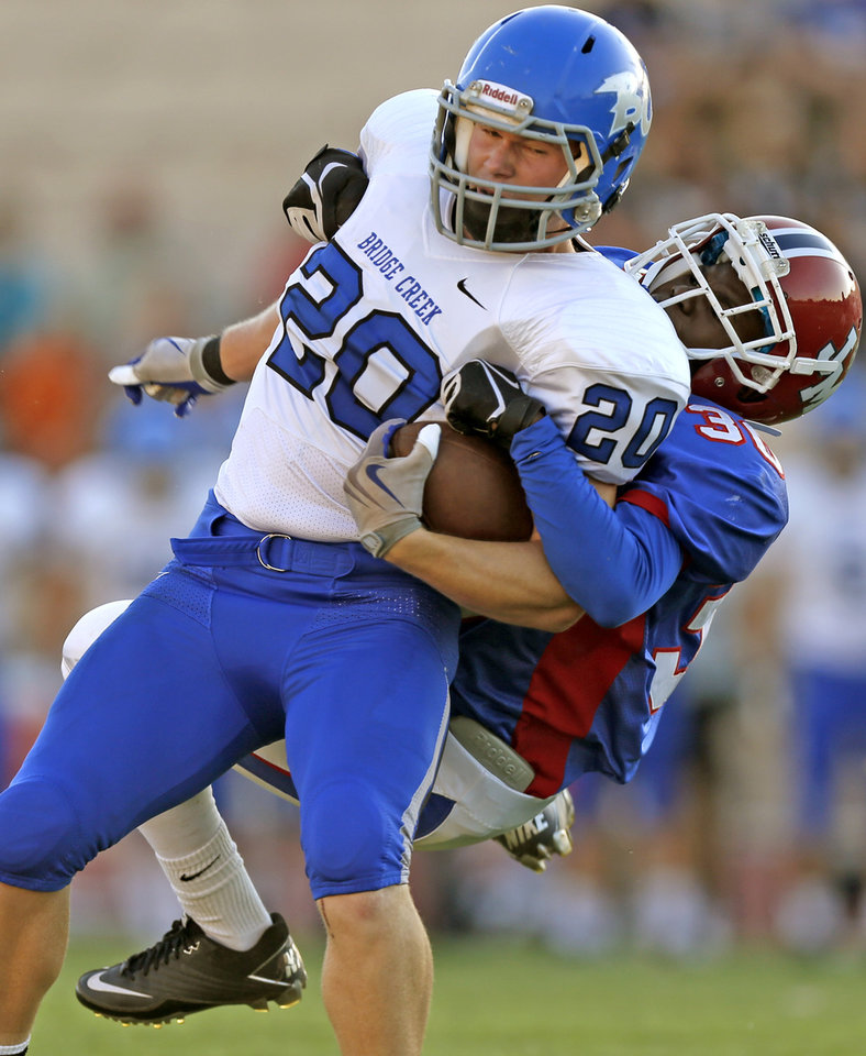 Bridge Creek\'s Morgan Merrell fights off John Marshall\'s Carltrell Parker during a high school football game at Taft Stadium in Oklahoma City, Thursday, September 6, 2012. Photo by Bryan Terry, The Oklahoman