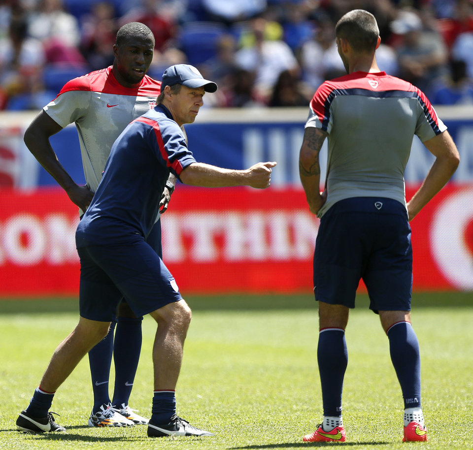 Photo - United States head coach Jurgen Klinsmann, center, talks to forwards Jozy Altidore, left, and Clint Dempsey during an open workout, Saturday, May 31, 2014, in Harrison, N.J. The United States are scheduled to Turkey in an international friendly soccer game on Sunday. (AP Photo/Julio Cortez)