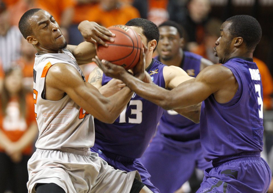 Oklahoma State's Markel Brown (22) fights for control with Kansas State's Angel Rodriguez (13), and Martavious Irving (3) during an NCAA college basketball game between the Oklahoma State University Cowboys (OSU) and the Kansas State University Wildcats (KSU) at Gallagher-Iba Arena in Stillwater, Okla., Saturday, Jan. 21, 2012. Photo by Bryan Terry, The Oklahoman