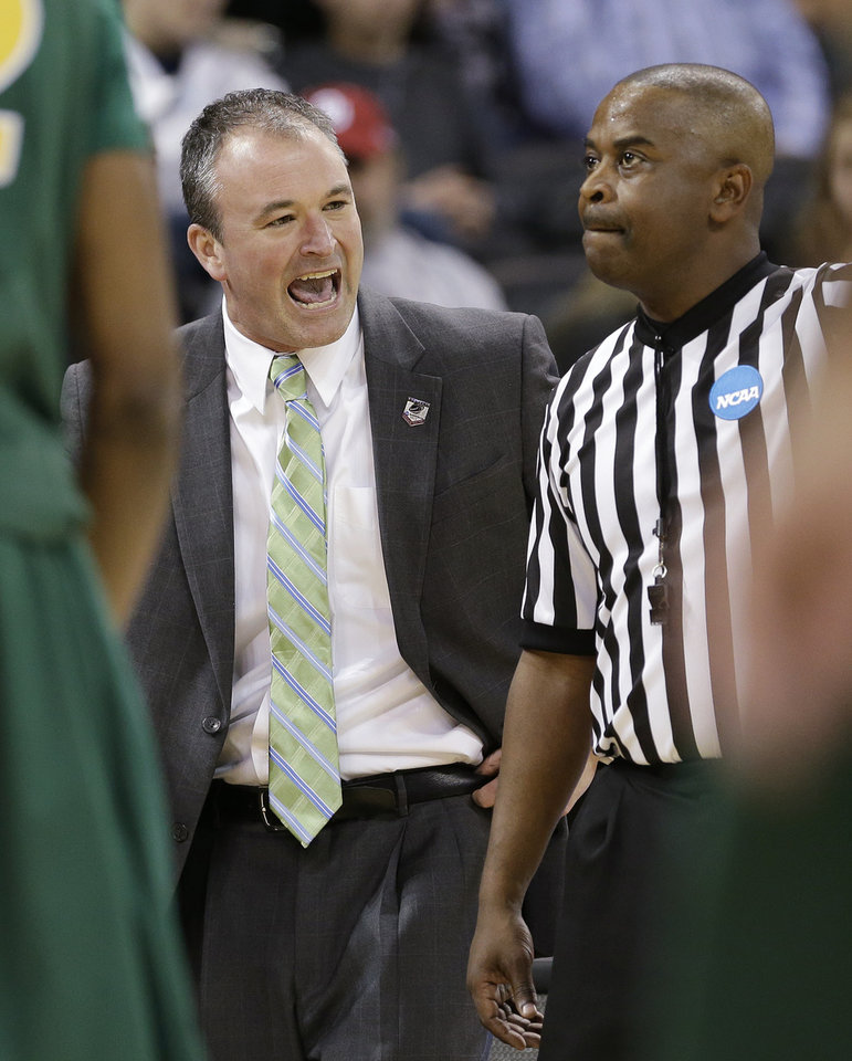 Photo - North Dakota State coach Saul Phillips, left, talks with an official in the first half against Oklahoma during the second round of the NCAA men's college basketball tournament, in Spokane, Wash., Thursday, March 20, 2014. (AP Photo/Elaine Thompson)