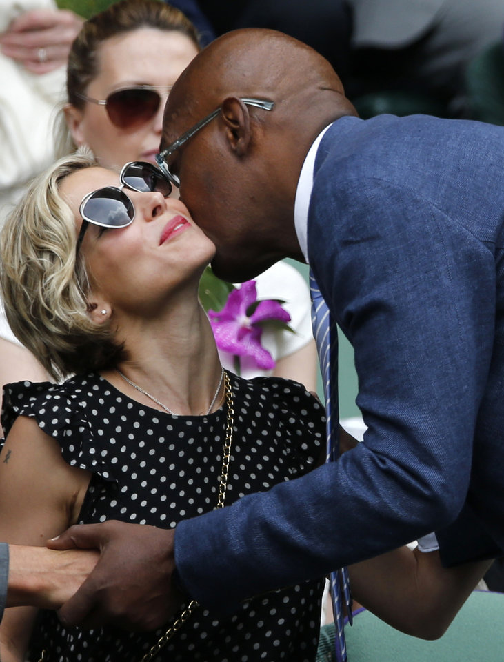 Photo - U.S actor Samuel L. Jackson, right, kisses Elsa Pataky as he arrives in the Royal Box prior to the men's singles final between Roger Federer of Switzerland and Novak Djokovic of Serbia on centre court at the All England Lawn Tennis Championships in Wimbledon, London, Sunday July 6, 2014. (AP Photo/Ben Curtis)