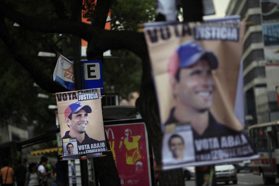 Election campaign posters promoting opposition presidential candidate Henrique Capriles hang on street polls in Caracas, Venezuela, Friday, Oct. 5, 2012. Venezuelans will head to the polls Sunday to vote in their country's presidential election, deciding on whether to keep President Hugo Chavez or seek change with Capriles. (AP Photo/Ariana Cubillos)