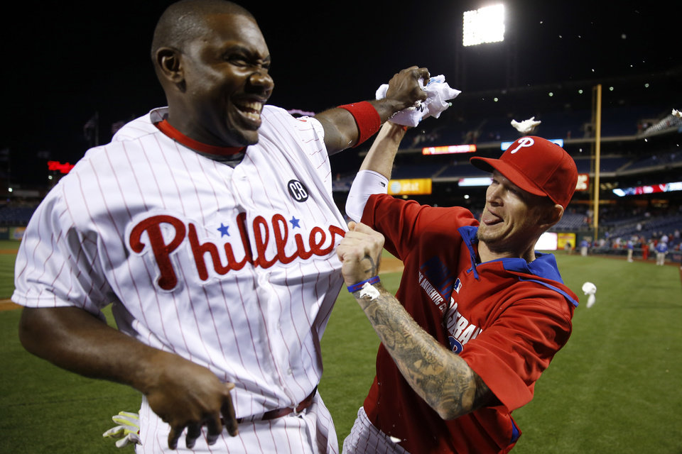 Photo - Philadelphia Phillies' A.J. Burnett, right, tries to hit Ryan Howard with a towel of shaving cream after Howard's game-winning three-run home run during the ninth inning of a baseball game against the Colorado Rockies, Wednesday, May 28, 2014, in Philadelphia. Philadelphia won 6-3. (AP Photo/Matt Slocum)
