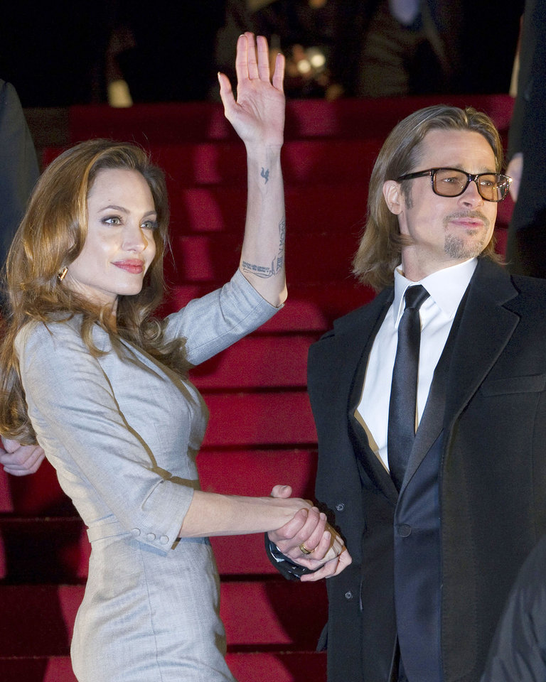 Photo - FILE - In this Monday, Feb. 13, 2012, file photo, U.S. actress and director Angelina Jolie, left, and U.S. actor Brad Pitt wave to the crowd as they arrive at the Cinema For Peace fundraising gala in Berlin. Jolie and Pitt were married Saturday, Aug. 23, 2014, in France, according to a spokesman for the couple. (AP Photo/Gero Breloer, File)